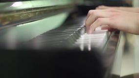 Νεαρός άνδρας που παίζει το πιάνο στενά χέρια επάνω ασκήσεις στο μουσικό όργανο Μουσικό όργανο πληκτρολογίων salfegio μακροχρόνιο απόθεμα βίντεο