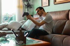 Νεαρός άνδρας που παίζει το τηλεοπτικό παιχνίδι που κρατά τον ασύρματο ελεγκτή στοκ φωτογραφίες