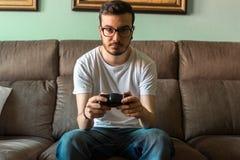 Νεαρός άνδρας που παίζει το τηλεοπτικό παιχνίδι που κρατά τον ασύρματο ελεγκτή στοκ εικόνα