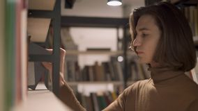 Νεαρός άνδρας που παίρνει ένα βιβλίο στο ράφι στη βιβλιοθήκη απόθεμα βίντεο