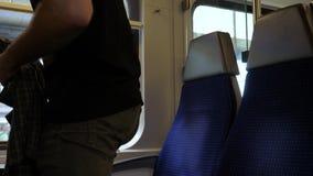 Νεαρός άνδρας που παίρνει ένα κάθισμα από το παράθυρο σε ένα τραίνο απόθεμα βίντεο