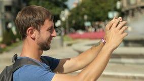 Νεαρός άνδρας που παίρνει την εικόνα στη συσκευή, περίεργος τουρίστας που φωτογραφίζει το ορόσημο απόθεμα βίντεο