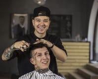 Νεαρός άνδρας που παίρνει το κούρεμα από τον ευτυχή κουρέα καθμένος στην καρέκλα στο barbershop Στοκ Εικόνες