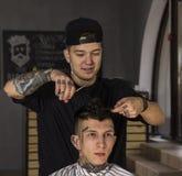 Νεαρός άνδρας που παίρνει το κούρεμα από τον ευτυχή κουρέα καθμένος στην καρέκλα στο barbershop Στοκ φωτογραφίες με δικαίωμα ελεύθερης χρήσης