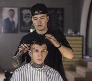 Νεαρός άνδρας που παίρνει το κούρεμα από τον κουρέα καθμένος στην καρέκλα στο barbershop Στοκ εικόνα με δικαίωμα ελεύθερης χρήσης
