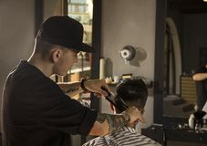 Νεαρός άνδρας που παίρνει το κούρεμα από τον κουρέα καθμένος στην καρέκλα στο barbershop Στοκ εικόνες με δικαίωμα ελεύθερης χρήσης