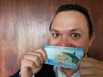 νεαρός άνδρας που παρουσιάζει και που κρατά από την Κόστα Ρίκα τραπεζογραμμάτιο των colones του 2000 στοκ φωτογραφίες