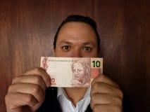 νεαρός άνδρας που παρουσιάζει και που κρατά βραζιλιάνο τραπεζογραμμάτιο δέκα reais στοκ φωτογραφίες