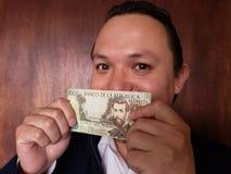 νεαρός άνδρας που παρουσιάζει και που κρατά κολομβιανό τραπεζογραμμάτιο 5000 πέσων στοκ εικόνα με δικαίωμα ελεύθερης χρήσης