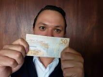 νεαρός άνδρας που παρουσιάζει και που κρατά σουηδικό τραπεζογραμμάτιο του kronor πενήντα στοκ φωτογραφίες με δικαίωμα ελεύθερης χρήσης