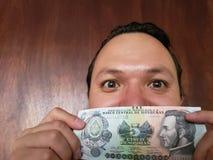 νεαρός άνδρας που παρουσιάζει και που κρατά τραπεζογραμμάτιο Ονδουριανών πέντε Lempira στοκ φωτογραφία