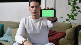 Νεαρός άνδρας που παρουσιάζει τηλέφωνο ` s κυττάρων του κενή πράσινη οθόνη Στοκ Εικόνες