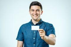 Νεαρός άνδρας που παρουσιάζει την κενό επαγγελματική κάρτα ή σημάδι Στοκ εικόνες με δικαίωμα ελεύθερης χρήσης
