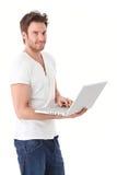 Νεαρός άνδρας που περιοδεύει Διαδίκτυο στο χαμόγελο lap-top Στοκ εικόνες με δικαίωμα ελεύθερης χρήσης