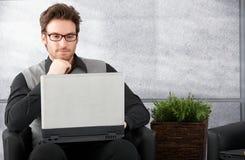 Νεαρός άνδρας που περιοδεύει Διαδίκτυο στο lap-top Στοκ εικόνες με δικαίωμα ελεύθερης χρήσης
