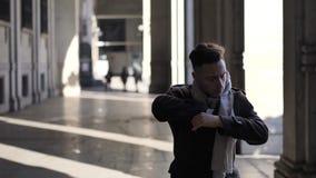 Νεαρός άνδρας που περπατά και που φορά το μαντίλι κάτω από την κιονοστοιχία απόθεμα βίντεο