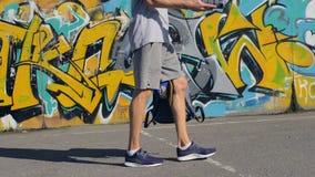 Νεαρός άνδρας που περπατά κατά μήκος του εδάφους οδών με ένα μεταλλικό κουτί αερολύματος στα χέρια του απόθεμα βίντεο