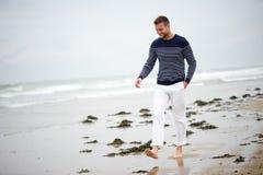 Νεαρός άνδρας που περπατά στην παραλία Στοκ Εικόνες