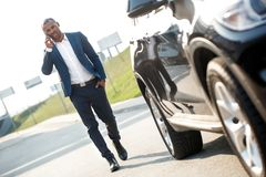 Νεαρός άνδρας που περπατά στο αυτοκίνητο που μιλά στο smartphone σοβαρό στοκ εικόνα με δικαίωμα ελεύθερης χρήσης
