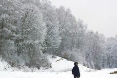 Νεαρός άνδρας που περπατά στο χειμερινό δάσος στοκ φωτογραφία με δικαίωμα ελεύθερης χρήσης