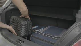 Νεαρός άνδρας που προετοιμάζει τις τσάντες ταξιδιού του μέσα στον κορμό του αυτοκινήτου έτοιμο για τις διακοπές - φιλμ μικρού μήκους