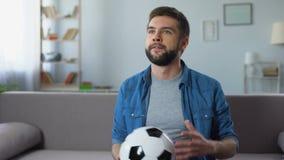 Νεαρός άνδρας που προσέχει νευρικά τον αγώνα ποδοσφαίρου στο σπίτι TV, που ματαιώνεται με την απώλεια ομάδων φιλμ μικρού μήκους
