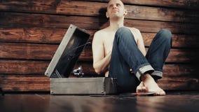 Νεαρός άνδρας που προσποιείται να ακούσει παλαιό gramophone στο σπίτι φιλμ μικρού μήκους