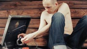 Νεαρός άνδρας που προσποιείται να ακούσει παλαιό gramophone στο σπίτι απόθεμα βίντεο