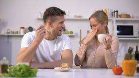 Νεαρός άνδρας που προσποιείται να ταΐσει το κορίτσι με το κέικ, ζεύγος που έχει τη διασκέδαση στην κουζίνα, φλερτ απόθεμα βίντεο