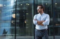 Νεαρός άνδρας που στέκεται ενάντια στο σύγχρονο κτήριο στοκ εικόνες