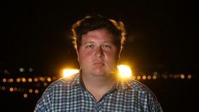 Νεαρός άνδρας που στέκεται και που εξετάζει τη κάμερα τη νύχτα υπαίθριος απόθεμα βίντεο