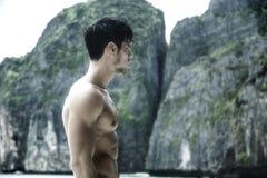 Νεαρός άνδρας που στέκεται στην άκρη του ωκεανού Στοκ Εικόνα