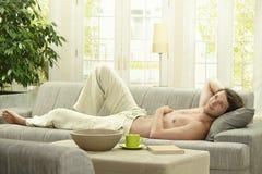 Νεαρός άνδρας που στηρίζεται στον καναπέ Στοκ φωτογραφία με δικαίωμα ελεύθερης χρήσης