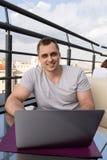 Νεαρός άνδρας που συνδέει με ένα lap-top στον καφέ Πόλης κτήρια στο υπόβαθρο στοκ εικόνες