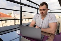 Νεαρός άνδρας που συνδέει με ένα lap-top στον καφέ Πόλης κτήρια στο υπόβαθρο στοκ εικόνες με δικαίωμα ελεύθερης χρήσης