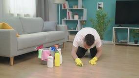 Νεαρός άνδρας που τακτοποιεί μετά από να κινηθεί προς το νέο διαμέρισμα Νέα έννοια εγχώριου καθαρισμού απόθεμα βίντεο