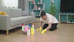 Νεαρός άνδρας που τακτοποιεί μετά από να κινηθεί προς το νέο διαμέρισμα Νέα έννοια εγχώριου καθαρισμού φιλμ μικρού μήκους
