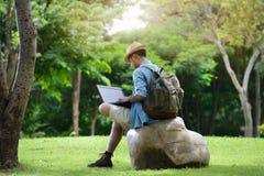 Νεαρός άνδρας που ταξιδεύει και που εργάζεται στο lap-top Στοκ εικόνες με δικαίωμα ελεύθερης χρήσης