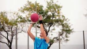 Νεαρός άνδρας που τρέχει με μια σφαίρα και που ρίχνει μια σφαίρα στο καλάθι επιτυχώς πετώντας στεφάνη παιχνιδιών καλαθοσφαίρισης  απόθεμα βίντεο