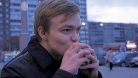 Νεαρός άνδρας που τρώει δαγκώνοντας ένα νόστιμο χάμπουργκερ γρήγορου φαγητού burger οδών Νεαρός άνδρας που τρώει Burger στην οδό Στοκ Φωτογραφία