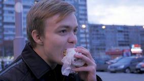 Νεαρός άνδρας που τρώει δαγκώνοντας ένα νόστιμο χάμπουργκερ γρήγορου φαγητού burger οδών Νεαρός άνδρας που τρώει Burger στην οδό Στοκ εικόνα με δικαίωμα ελεύθερης χρήσης