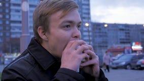 Νεαρός άνδρας που τρώει δαγκώνοντας ένα νόστιμο χάμπουργκερ γρήγορου φαγητού burger οδών Νεαρός άνδρας που τρώει Burger στην οδό Στοκ Φωτογραφίες