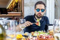 Νεαρός άνδρας που τρώει τη φυτικά σαλάτα και το pulpo ένα Λα Gallega με τις πατάτες Στοκ εικόνες με δικαίωμα ελεύθερης χρήσης