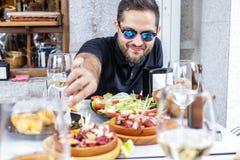 Νεαρός άνδρας που τρώει Pulpo ένα Λα Gallega με τις πατάτες Της Γαλικίας πιάτα χταποδιών Στοκ εικόνες με δικαίωμα ελεύθερης χρήσης