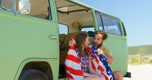Νεαρός άνδρας που τυλίγει την όμορφη γυναίκα με τη αμερικανική σημαία 4k απόθεμα βίντεο