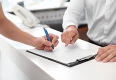 Νεαρός άνδρας που υπογράφει τα έγγραφα στο σαλόνι στοκ φωτογραφία με δικαίωμα ελεύθερης χρήσης