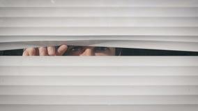 Νεαρός άνδρας που φαίνεται έξω το παράθυρο μέσω των τυφλών στην οδό φιλμ μικρού μήκους