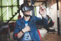 Νεαρός άνδρας που φορά τα γυαλιά εικονικής πραγματικότητας στο σύγχρονο εσωτερικό coworking στούντιο σχεδίου Smartphone χρησιμοπο Στοκ εικόνες με δικαίωμα ελεύθερης χρήσης