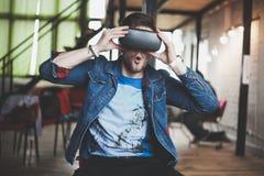 Νεαρός άνδρας που φορά τα γυαλιά εικονικής πραγματικότητας στο σύγχρονο εσωτερικό coworking στούντιο σχεδίου Smartphone χρησιμοπο Στοκ Εικόνα