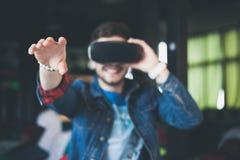 Νεαρός άνδρας που φορά τα γυαλιά εικονικής πραγματικότητας στο σύγχρονο εσωτερικό coworking στούντιο σχεδίου Smartphone χρησιμοπο Στοκ Φωτογραφίες